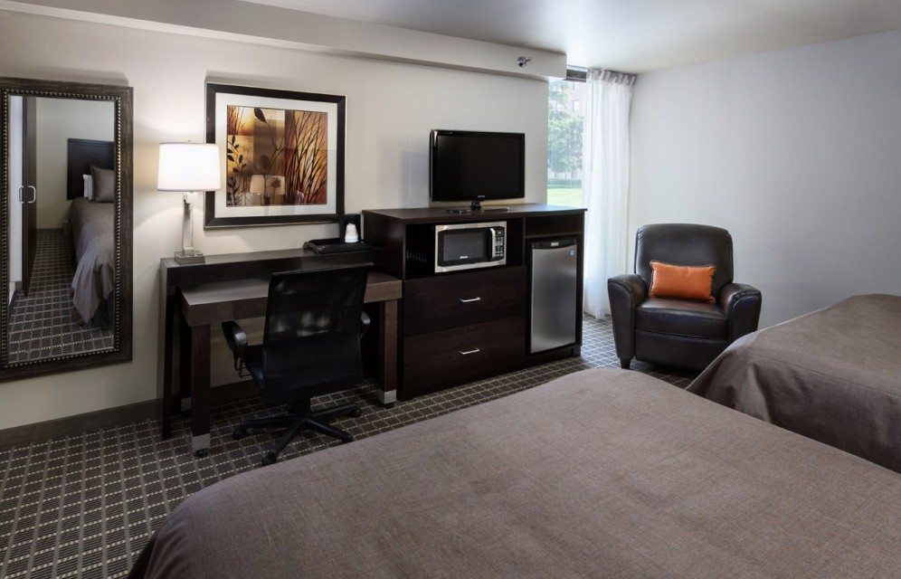 Two beds, desk, tv, microwave, fridge, and chair