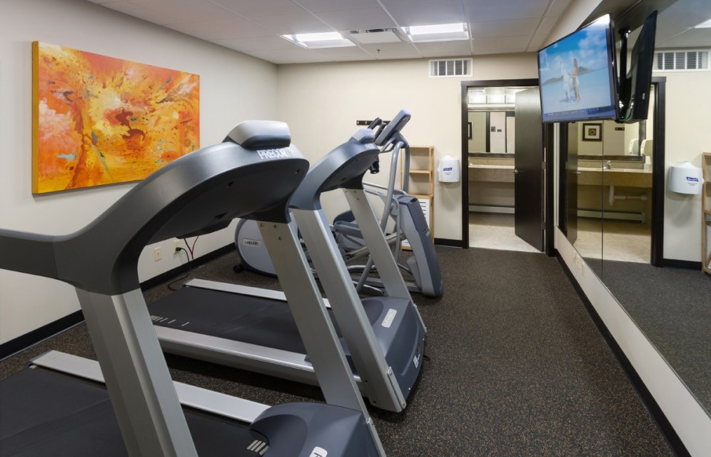Fitness Room with treadmills, elliptical, bike, and tv